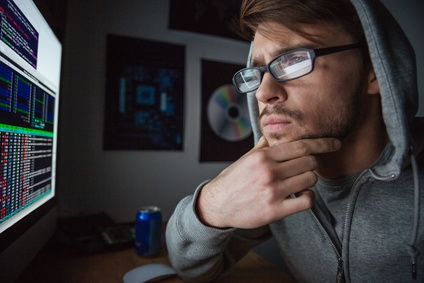 Pensive man in sweatshirt with hood thinking and coding