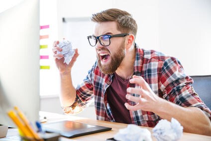 Angry crazy designer yelling and crumpling paper on his workplace