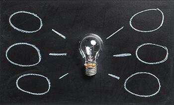 Glühbirne mit Sprechblasen Denkblasen und Ideen